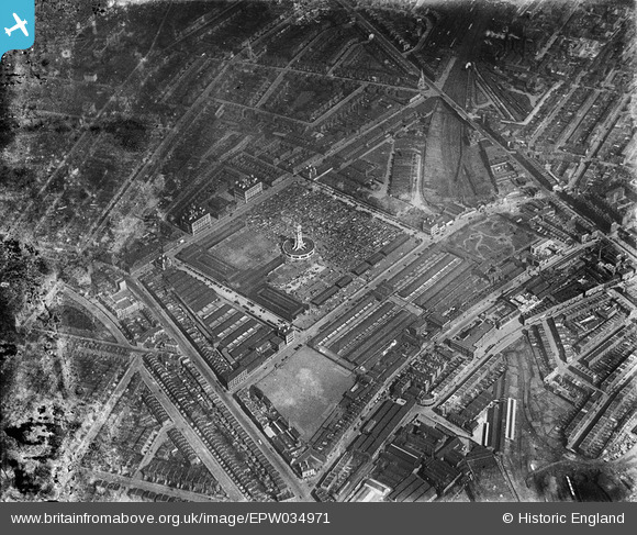 [a black-and-white aerial photograph of the market in 1931,  stalls and the clocktower with octagonal offices at the base clearly visible]
